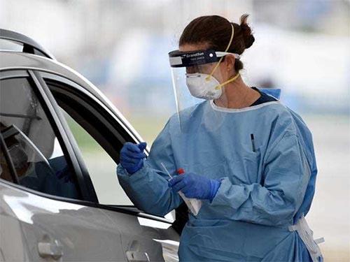 A nurse testing someone through a car window.